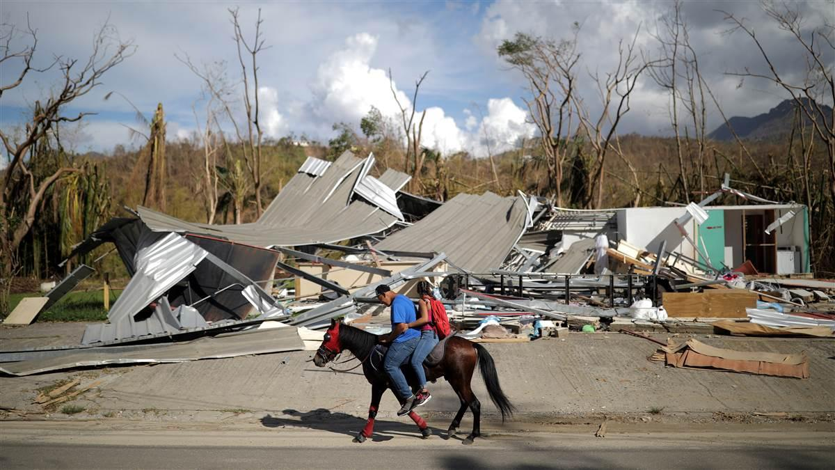 Local residents ride a horse by a destroyed building after Hurricane Maria in Jayuya, Puerto Rico, October 4, 2017. Photo by Carlos Barria, REUTERS.