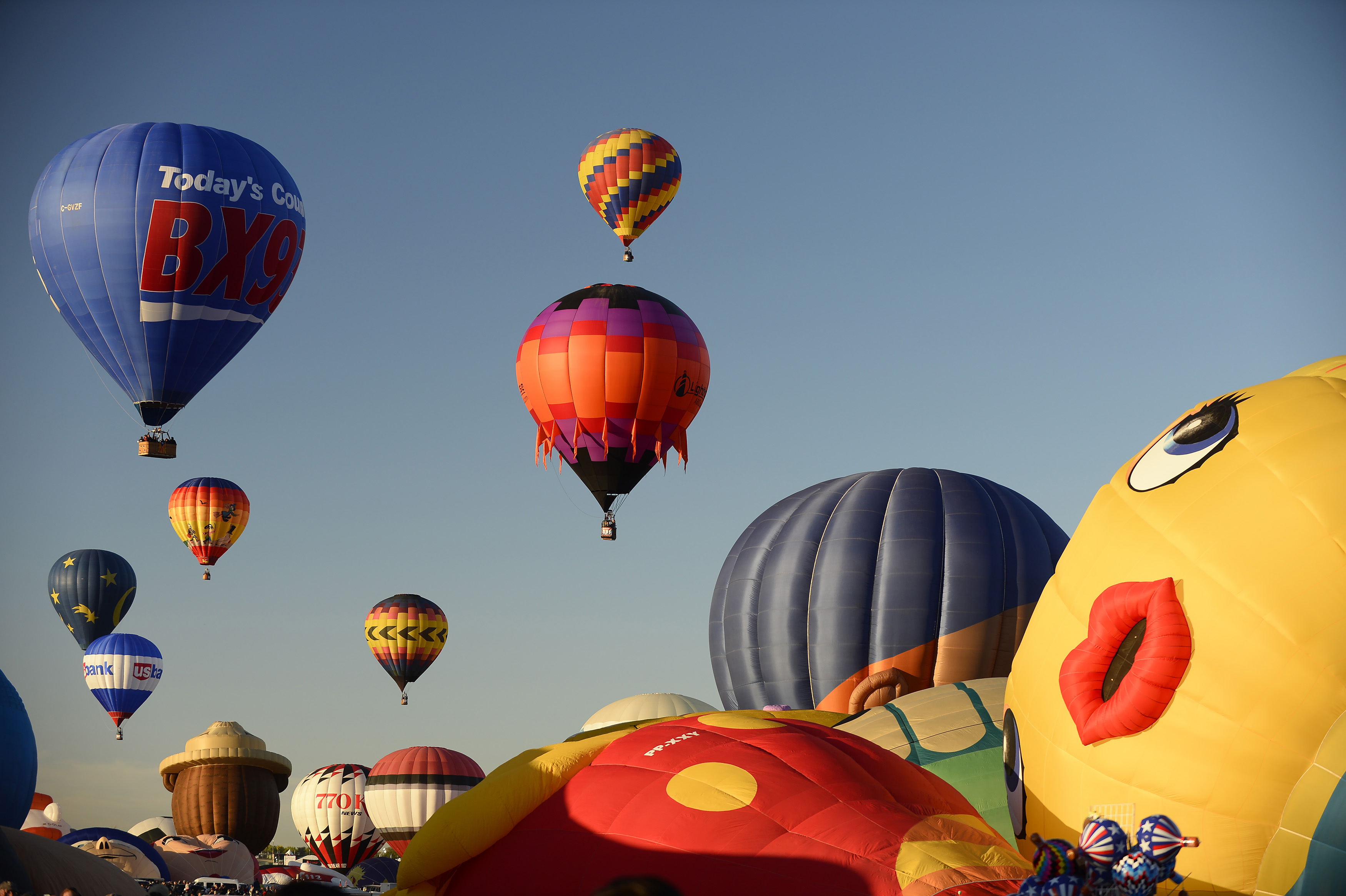 Balloonists lift off during a mass ascension at the 2016 Albuquerque International Balloon Fiesta. Photo by David Tulis.