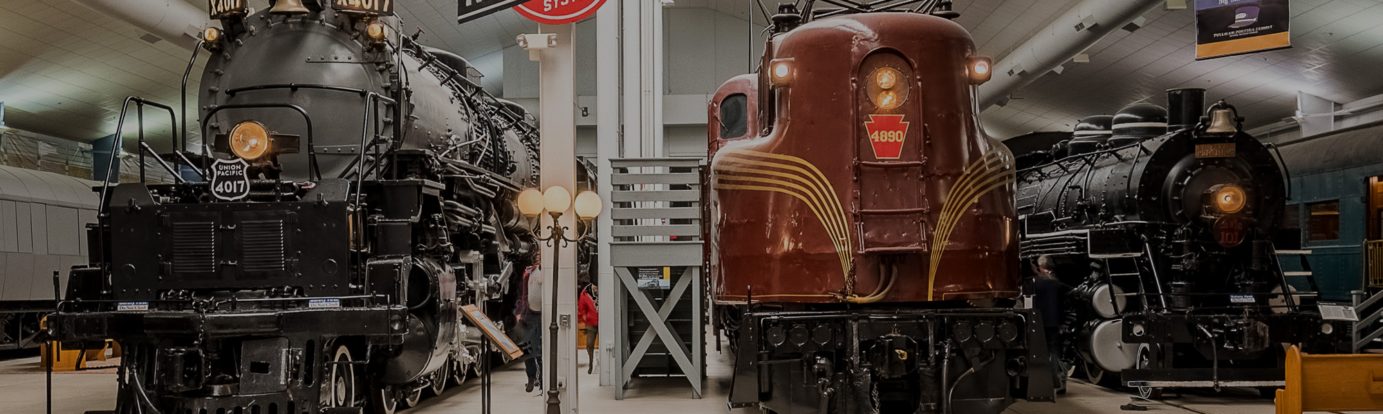 "Founded in 1956, the National Railroad Museum boasts an exceptional collection that includes many historic locomotives. Shown here are Union Pacific Big Boy No. 4017 (the ""Big Boys"" are the world's largest steam locomotives), PRR/Amtrak 4890, and U.S. Army 2-8-0 No. 101, used in Korea. The PRR's GG1 class of electric locomotive is one of the most iconic (steam, diesel, or electric) of all time. Sporting a beautiful streamlined design, the GG1s reached speeds of over 100 mph and ran for nearly 50 years after they first entered service during the mid-1930s. Photo courtesy National Railroad Museum."