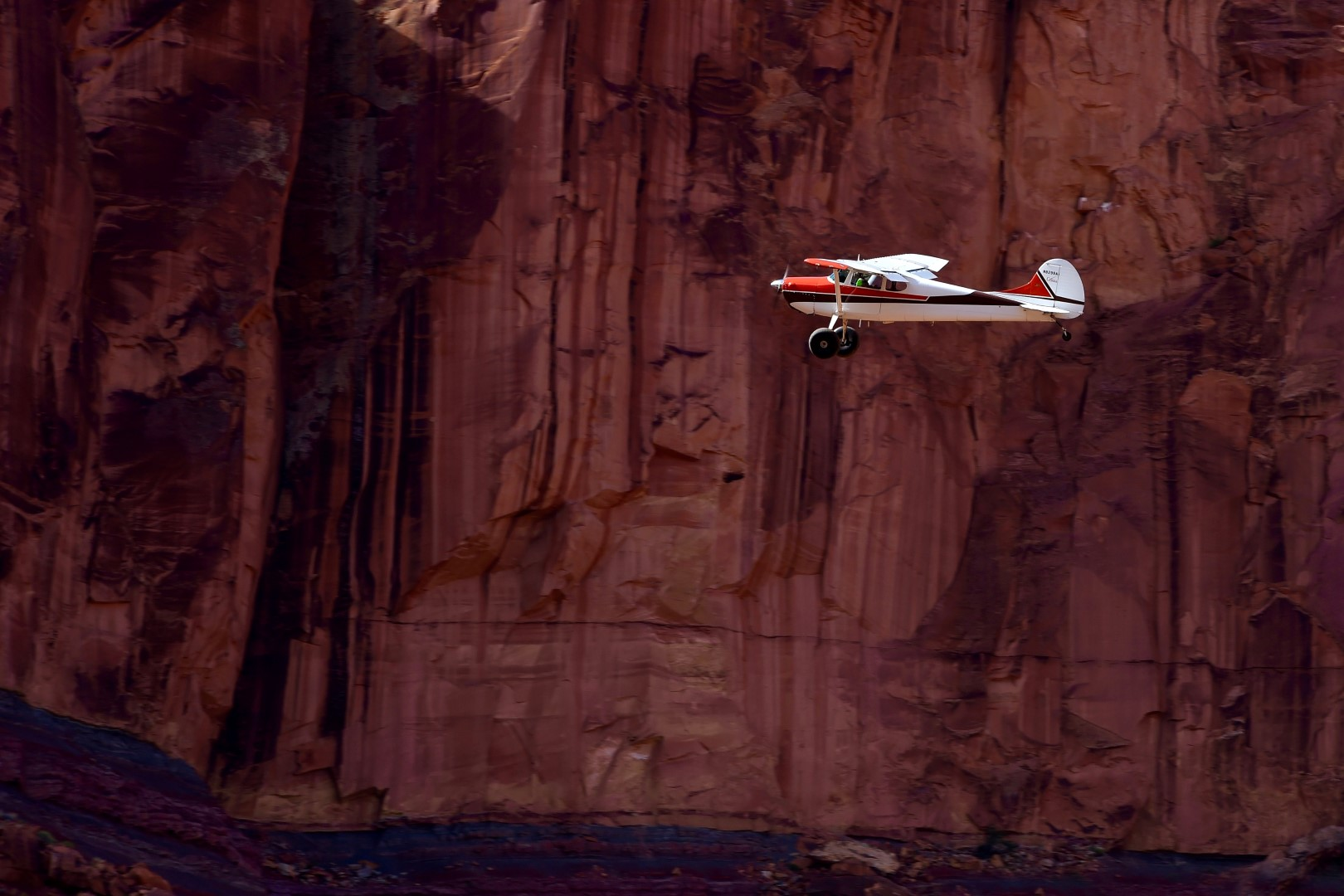 James Stevenson maneuvers in the canyon. Hidden Splendor is the perfect name for this gem of a backcountry airstrip, hidden deep inside a red rock canyon near a defunct uranium mine. The mine, originally named the Delta mine, was started in 1952 by Vernon Pick, an electrician from Minnesota. Pick sold the tremendously productive mine to Atlas Corporation, owned by Floyd Odlum, who renamed it Hidden Splendor. The landing strip was built during these boom years and has been used by aviators ever since. The mine became famous after a 1954 article in Life magazine but Atlas abandoned it in 1957 after production dropped. Photo by Brady Lane.