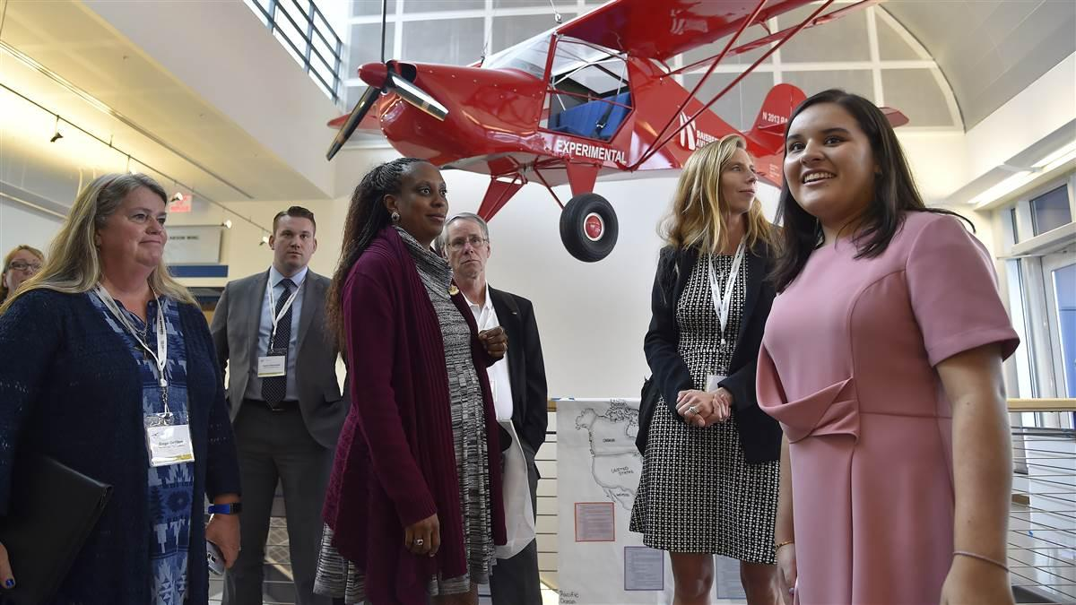 An Avid Flyer provides the background as Raisbeck Aviation High School student Nicole Diaz leads 2016 AOPA High School Symposium attendees on a tour. Photo by David Tulis.