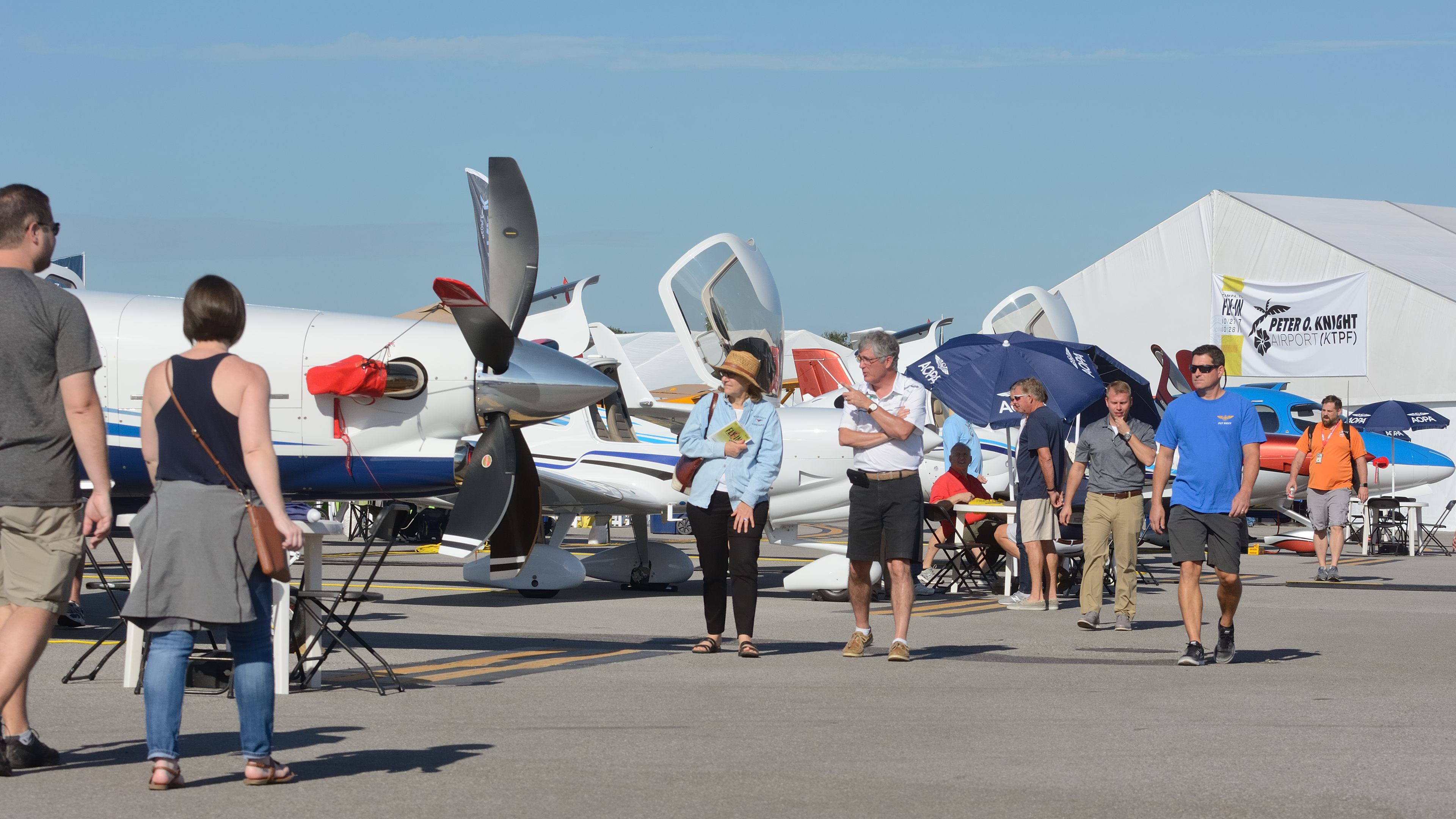 Visitors to AOPA's Tampa Fly-In stroll among the static display aircraft Saturday morning. The event was held at idyllic Peter O. Knight Airport, located on the city's waterfront. Photo by Mike Collins.