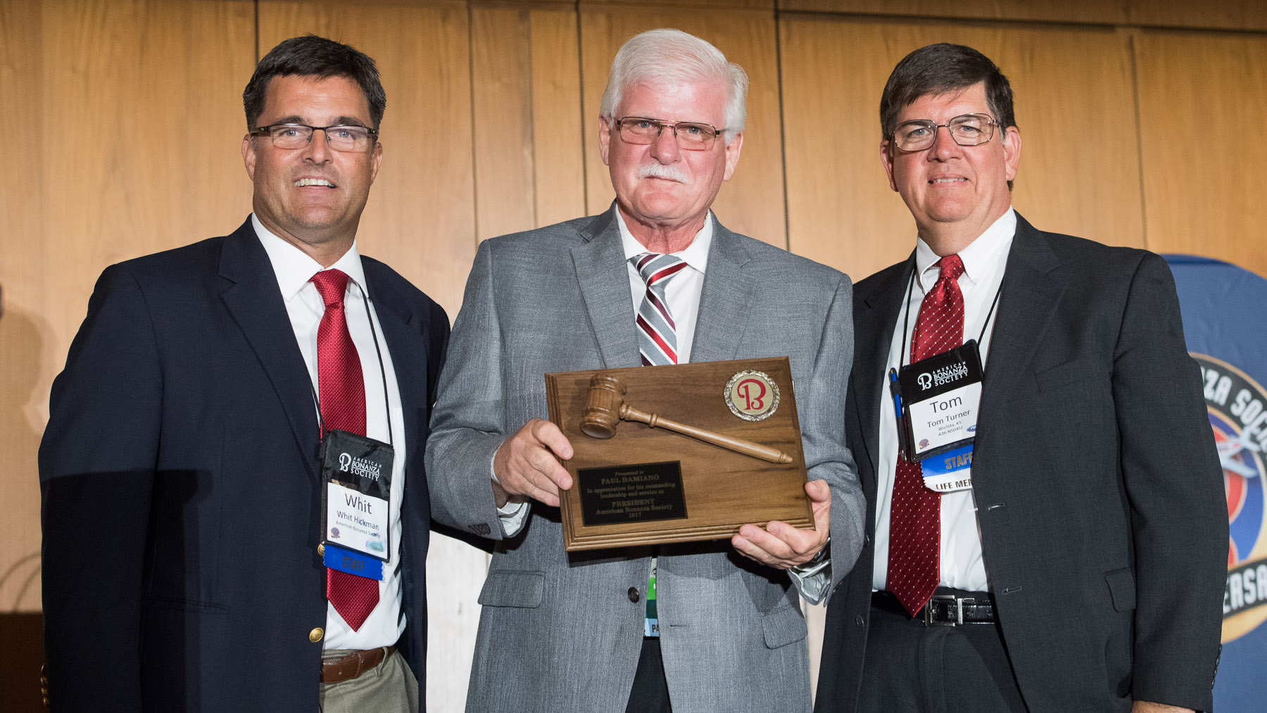 American Bonanza Society Executive Director Whit Hickman (left) and ABS Air Safety Foundation Executive Director Tom Turner (right) recognize the work of outgoing President Paul Damiano during the type club's fiftieth anniversary convention in Wichita. Photo courtesy of Visual Media Group.