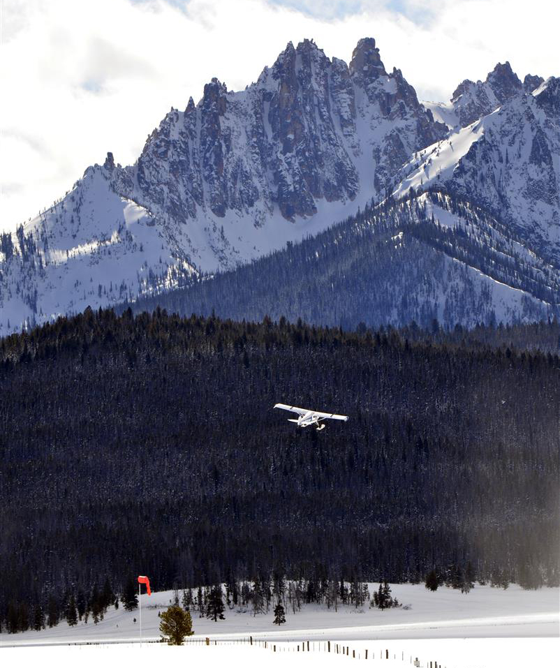 Against the dramatic background of the Sawtooth Mountains, a ski plane departs the snow runway at Stanley, Idaho, during the annual Stanley Ski Plane Fly-In, held each February. Photo by Santiago Guerricabeitia.