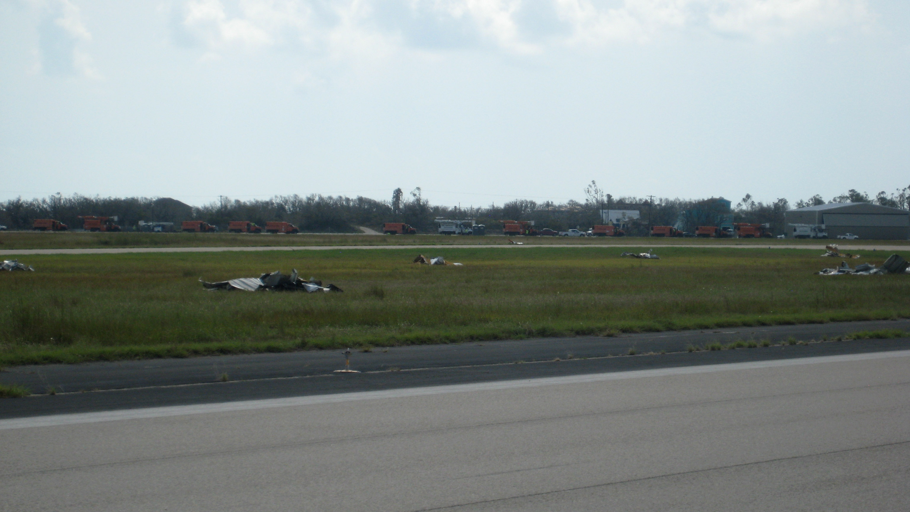 In Rockport, Texas, volunteers swept up piles of hangar debris. Orange FEMA trucks are in the background on the second runway. Photo by Larry Brown.