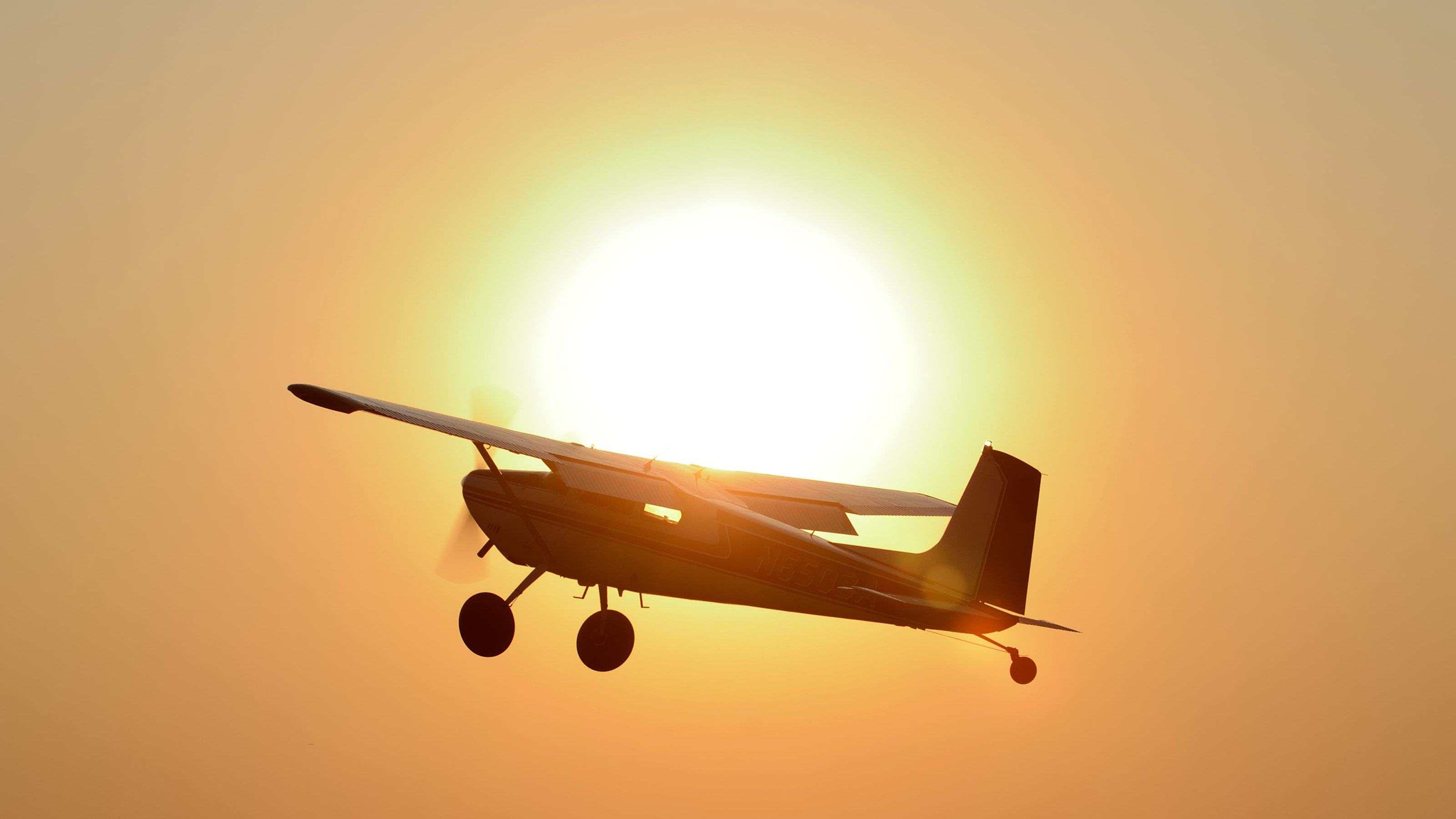A Cessna 180 climbs past the setting sun during the short takeoff and landing (STOL) demonstration held Friday evening at AOPA's 2017 Norman Fly-In. Photo by Mike Collins.
