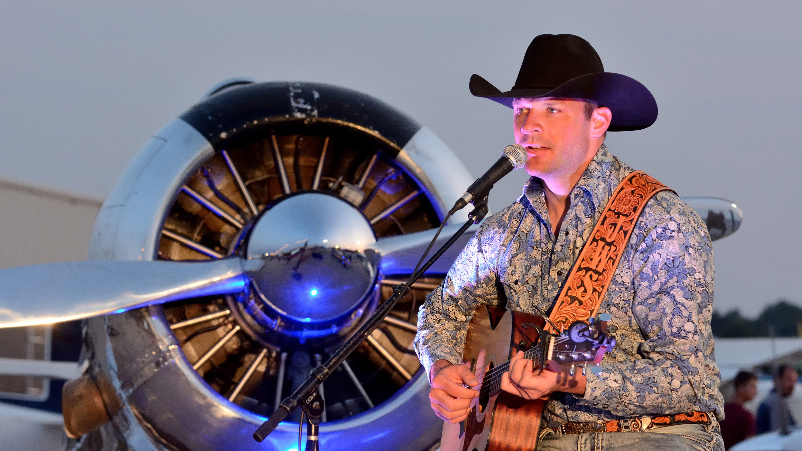Country singer John Wayne Schulz--who also is a pilot and an active flight instructor--entertains the crowd during Friday evening's Barnstormers Party at AOPA's 2017 Norman Fly-In. A North American T-6 serves as the backdrop. Photo by Mike Collins.