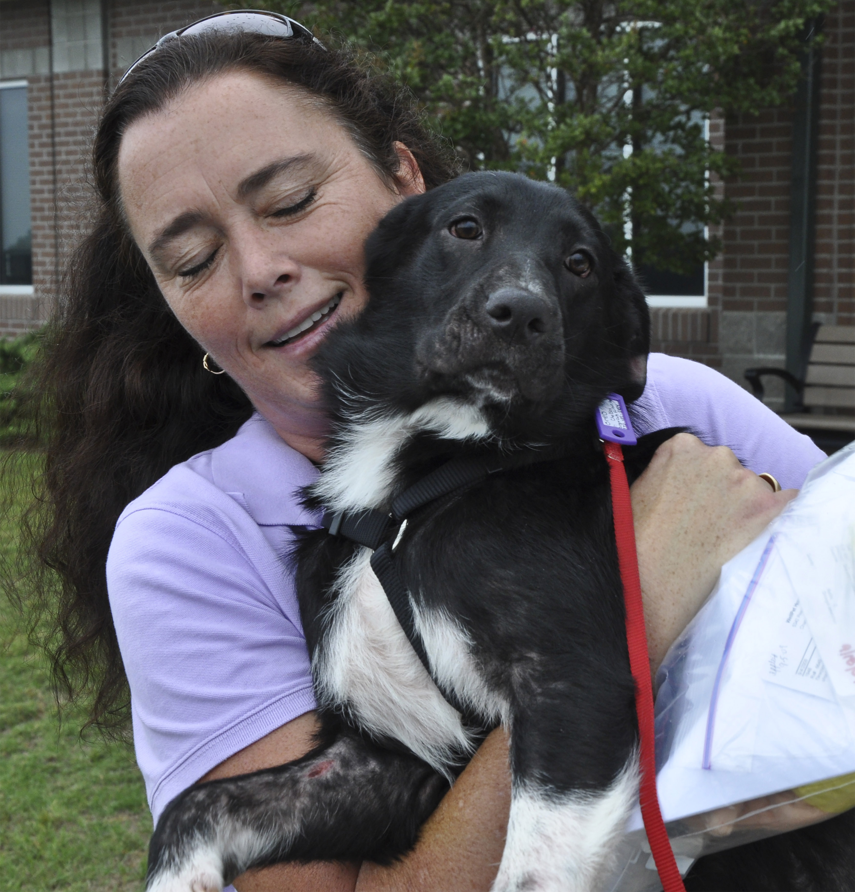 Oreo, a six-month-old female border collie, gets a last hug from her foster human Sabrina Sweeney-Garcia, who rescued Oreo from a north Georgia facility before the animal was to be put to sleep. Pilots N Paws is a volunteer organization that matches pilots and their aircraft with animals in need of new homes. Photo by David Tulis.