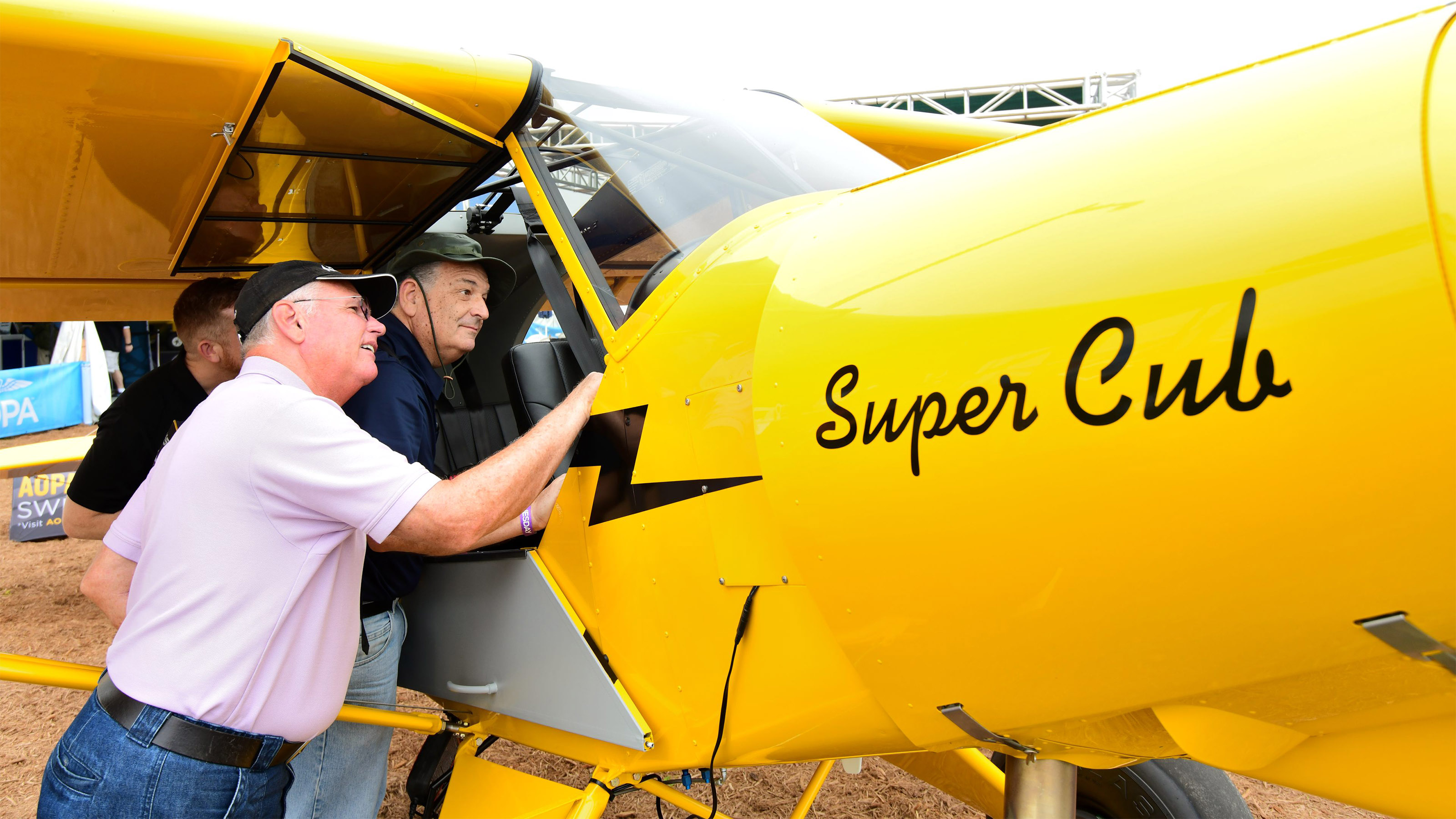 Visitors to the 2018 Sun 'n Fun International Fly-In and Expo inspect the cockpit of AOPA's Sweepstakes Super Cub. The airplane's refurbishment was completed by Baker Air Service in Baker, Mont., just in time for the airplane to be flown to Lakeland. Photo by Mike Collins.