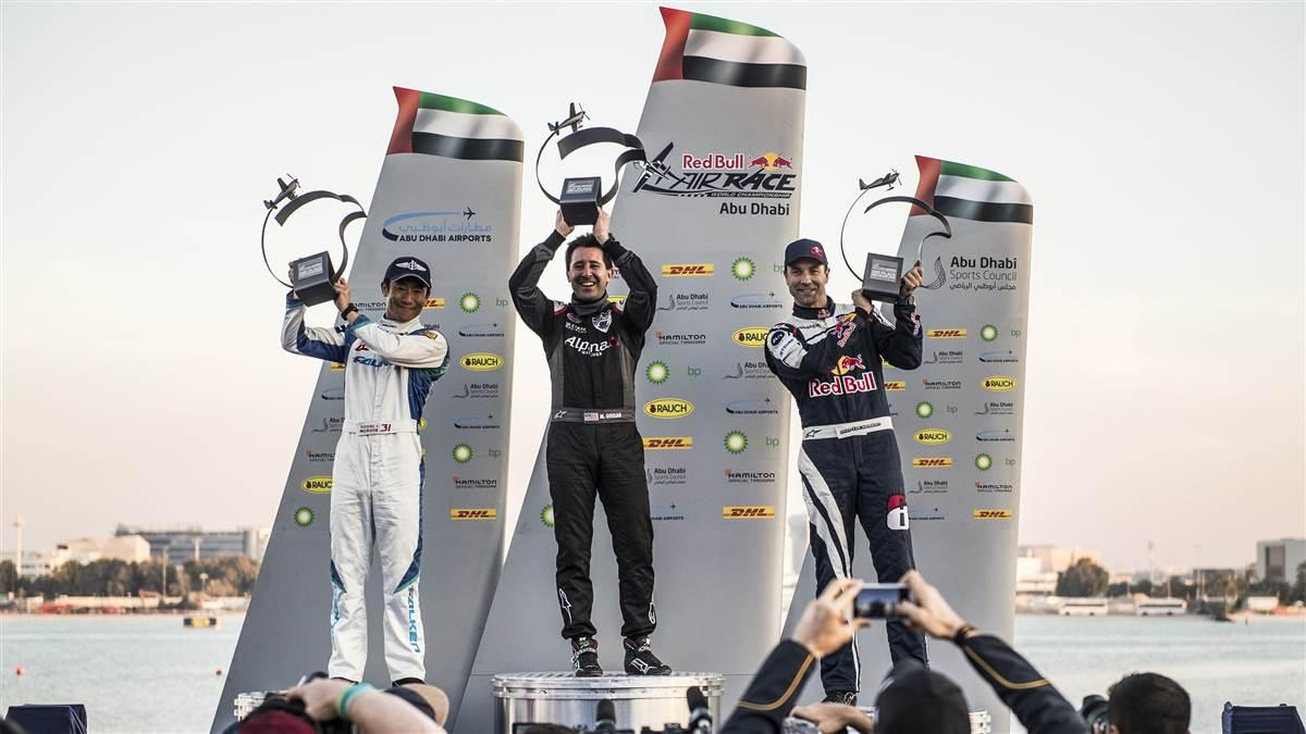 Michael Goulian of the United States (center) celebrates with Yoshihide Muroya of Japan (left) and Martin Sonka of the Czech Republic (right) during the Award Ceremony at the first round of the Red Bull Air Race World Championship in Abu Dhabi, United Arab Emirates on February 3, 2018. // Joerg Mitter / Red Bull Content Pool