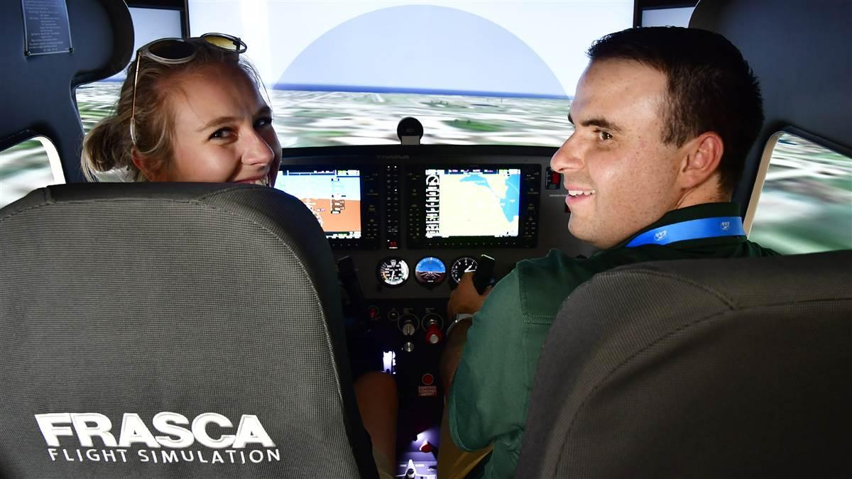 Utah Valley University students practice on a Frasca simulator during the company's sixtieth anniversary celebration luncheon at EAA AirVenture in Oshkosh, Wisconsin, July 25. Photo by David Tulis.