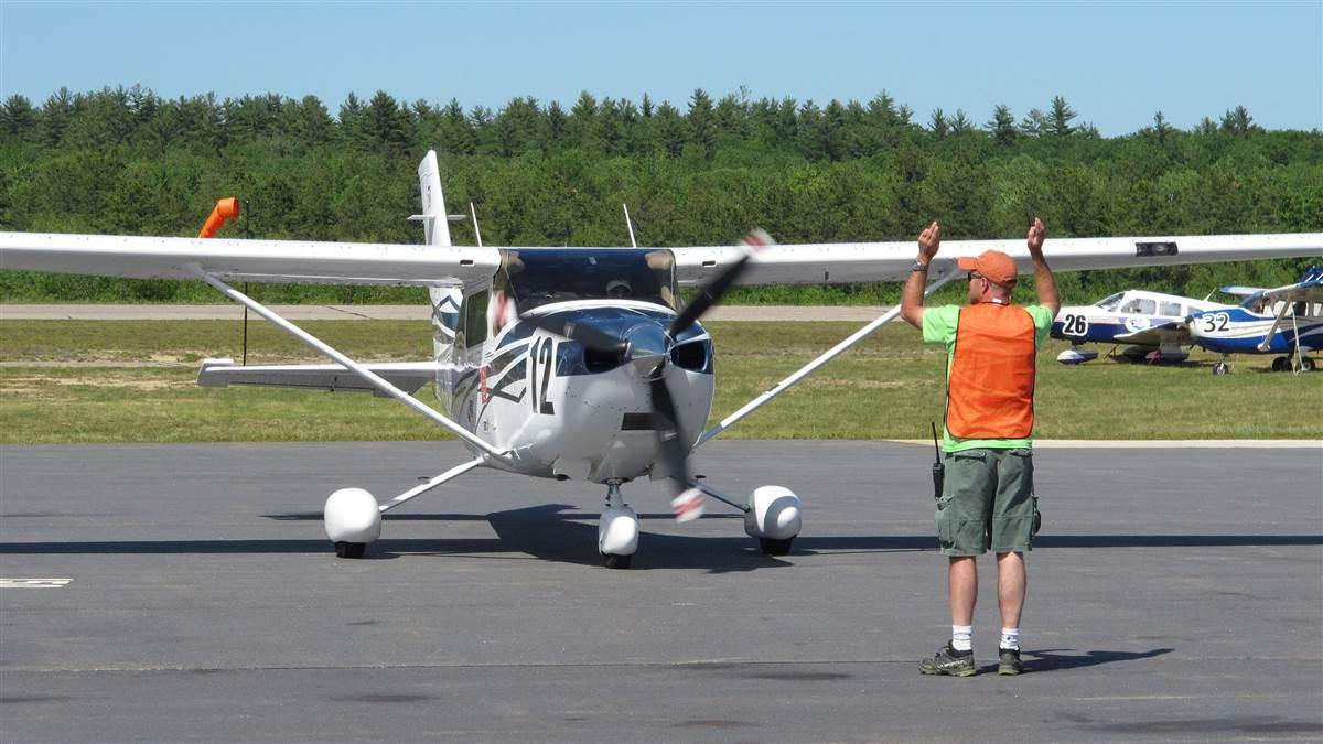 Lin Caywood and Bev Weintraub are marshaled to parking  after landing at Eastern Slope Regional Airport in Fryeburg, Maine, at the end of the Air Race Classic June 22. Photo by Dan Namowitz.