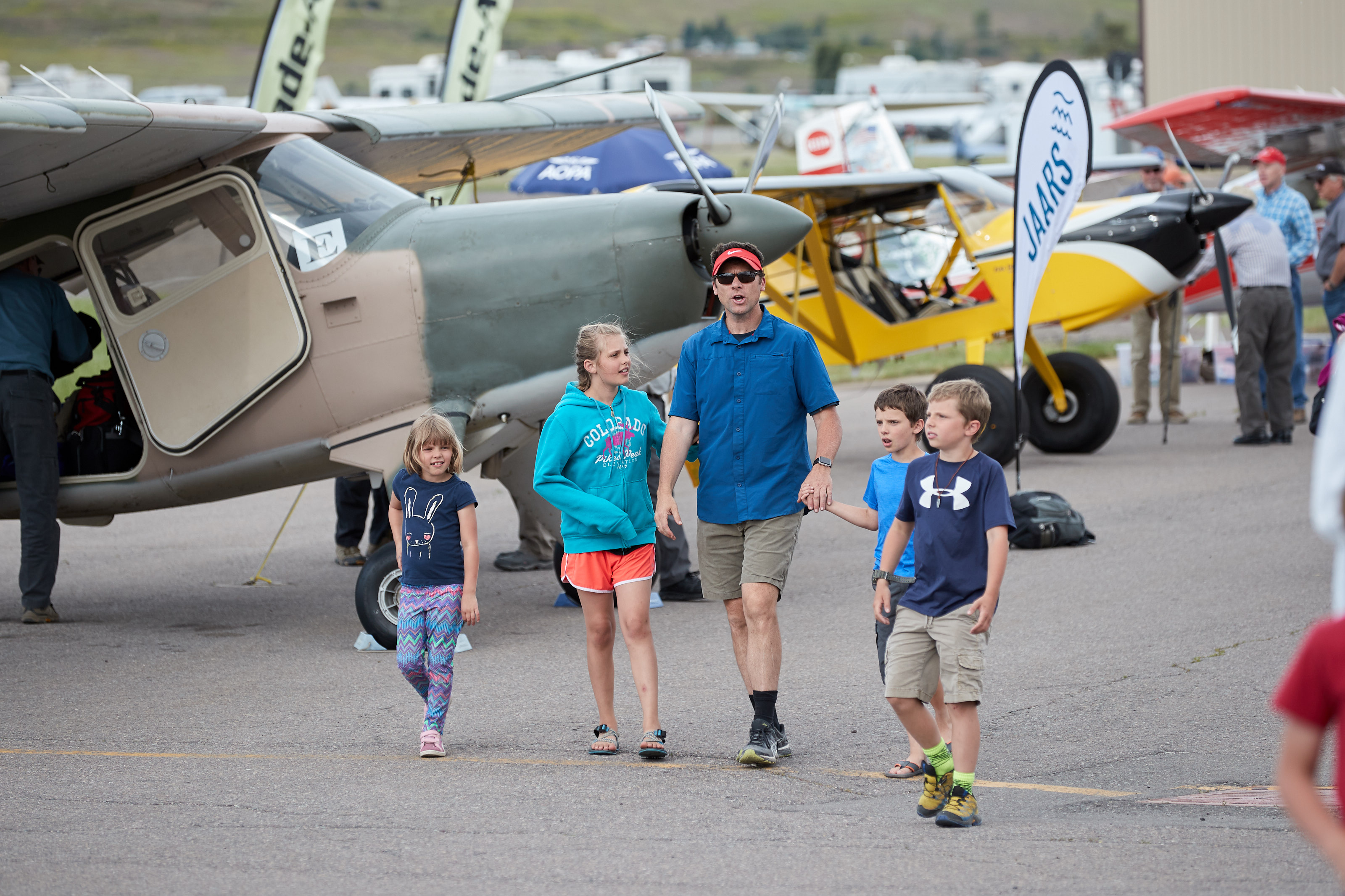 A family walks through the static display area during the AOPA Fly-In at Missoula International Airport, in Missoula, Montana. Photo by Mike Fizer.