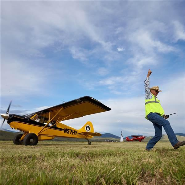 Aircraft wrangler Jimmie Gist orchestrates a short takeoff and landing demonstration with an Aviat Husky during the AOPA Fly-In at Missoula International Airport, in Missoula, Montana, June 15, 2018. Photo by Mike Fizer.