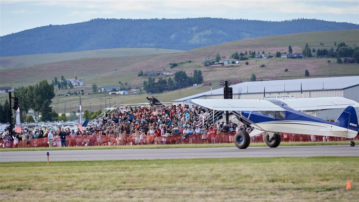 A crowd gathers for a short takeoff and landing demonstration during the AOPA Fly-In at Missoula, Montana. Photo by Mike Fizer.