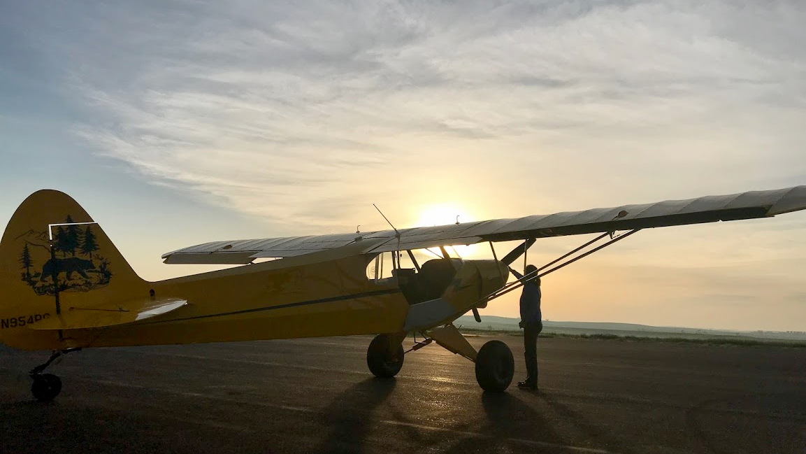 The sun rises as we finish preflighting the Super Cub for a 6 a.m. departure from Baker, Montana, to make it to Missoula before the weather deteriorates. Photo by Janet Davidson.