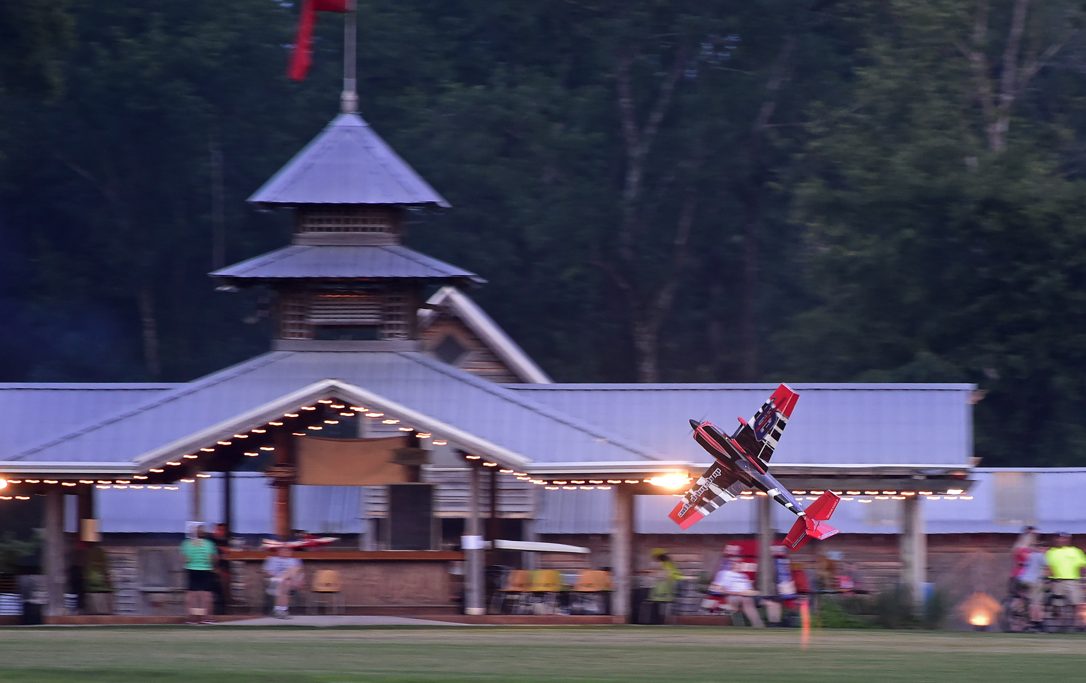A remote-controlled aerobatic demonstration takes place near the main gazebo during the Young Aviators Fly-In at Triple Tree Aerodrome June 8 to 10 in Woodruff, South Carolina. Photo by David Tulis.