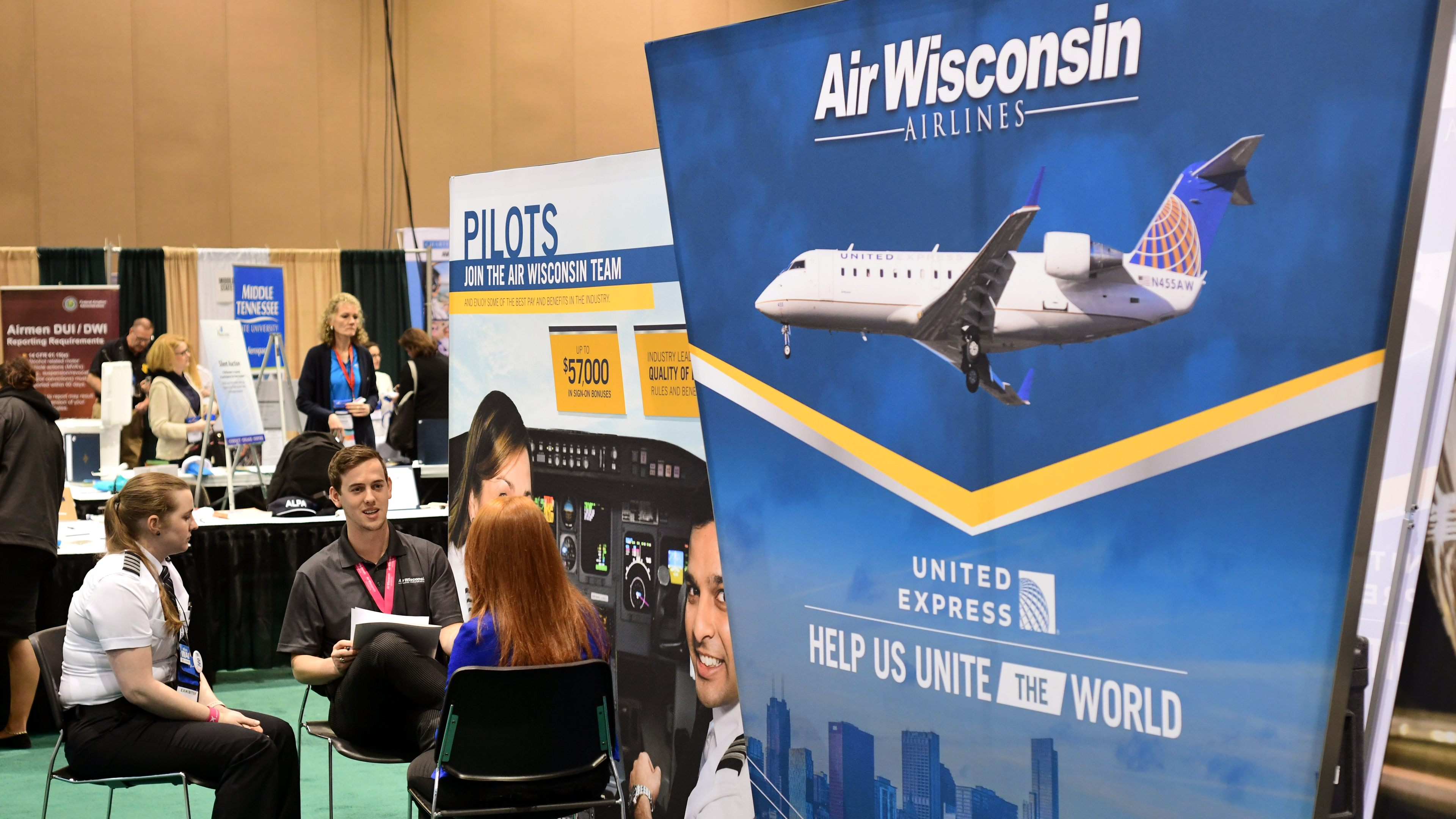 Two Air Wisconsin employees, including a captain (left), interview a pilot applicant behind the company's exhibit booth during the 2018 International Women in Aviation Conference in Reno, Nevada. Photo by Mike Collins.