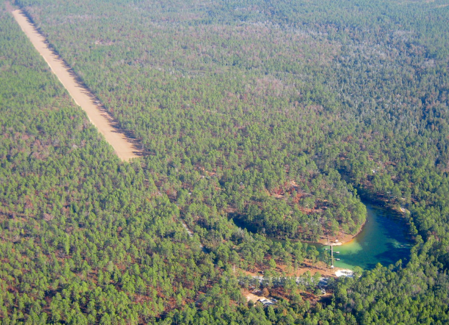 "This aerial photo, taken looking north, demonstrates how close the airstrip is to the Krul Recreation Area ""swimming hole,"" restrooms, and campground. Runway 18/36 is at 200 feet elevation and has 2,500 x 50 feet usable, with generous overruns at both ends. Photo by Bobby Capozzi."