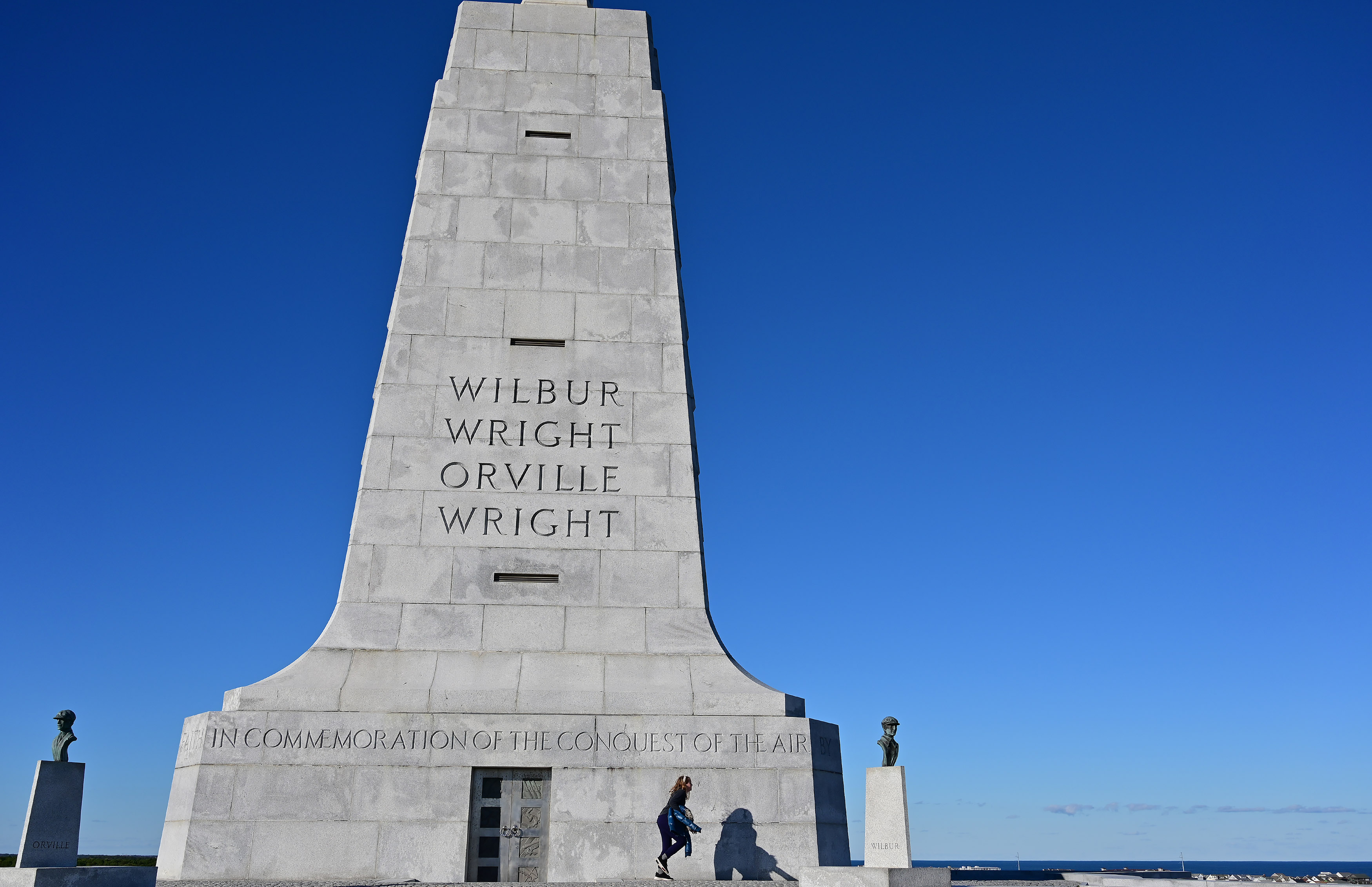 A youth explores the 60-foot monument at Kill Devil Hills at the Wright Brothers National Memorial in Kitty Hawk, North Carolina. A new visitors center, interactive exhibits, and a look at their bicycle building background await visitors to the Outer Banks memorial. Photo by David Tulis.