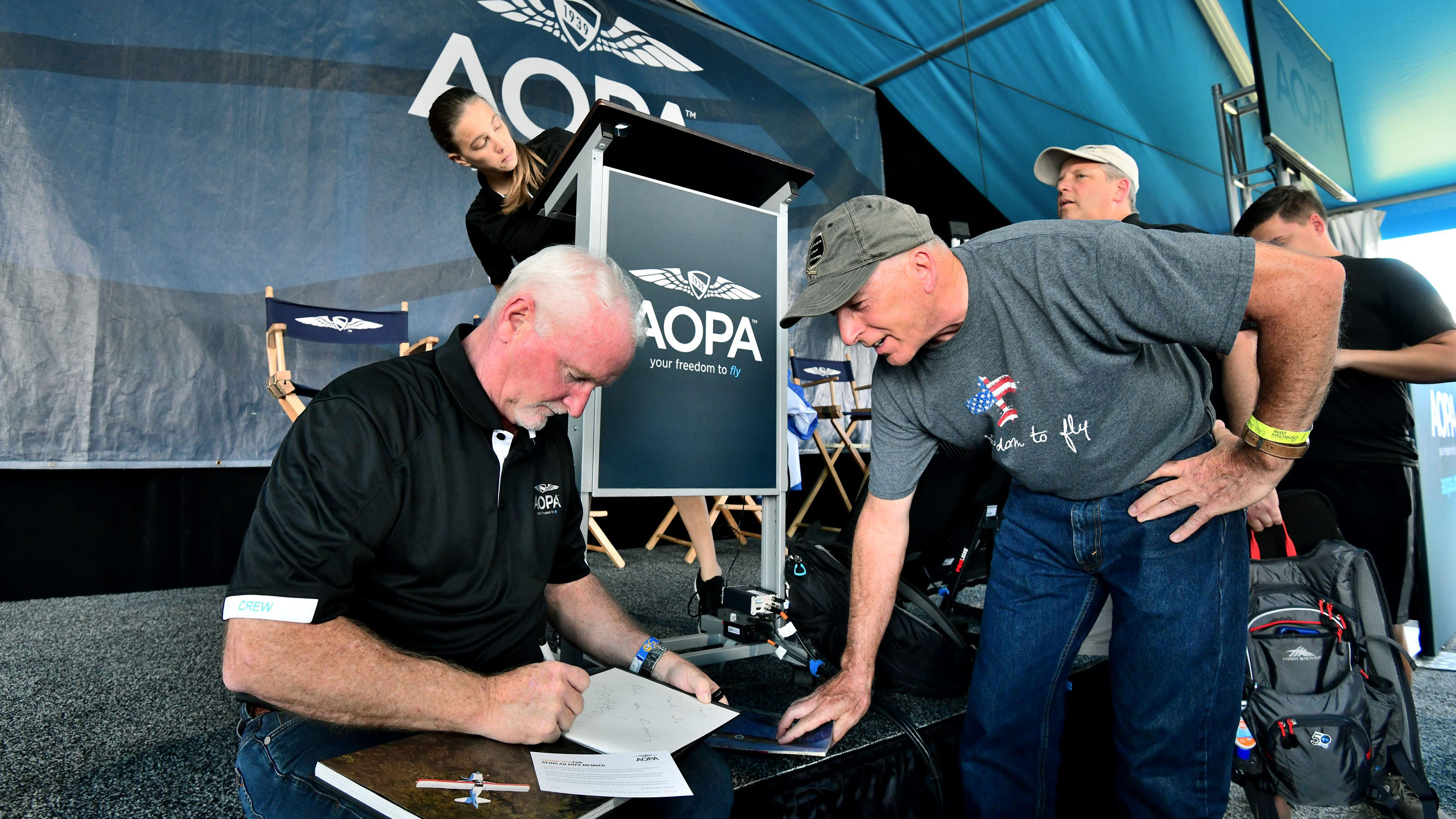 "After his EAA AirVenture Oshkosh Town Hall presentation, AOPA President Mark Baker, left, signs a copy of ""Freedom to Fly: AOPA and the History of General Aviation in America"" for David Pfeiffer of Indianapolis, Indiana. ""That is an excellent book. I read it all the way through,"" Pfeiffer said. Photo by Mike Collins."