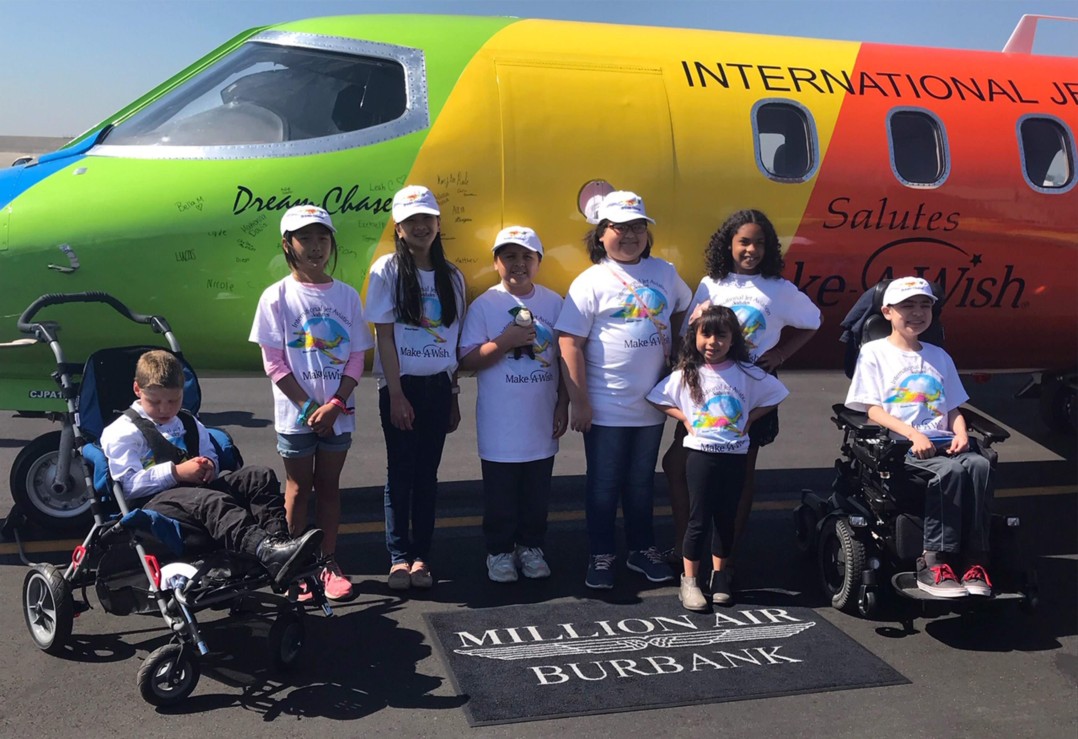 With some of their signatures on the fuselage behind them, Make-A-Wish recipients gather near a rainbow-colored 1982 Learjet 35A operated by International Jet Aviation. Photo courtesy of International Jet Aviation.