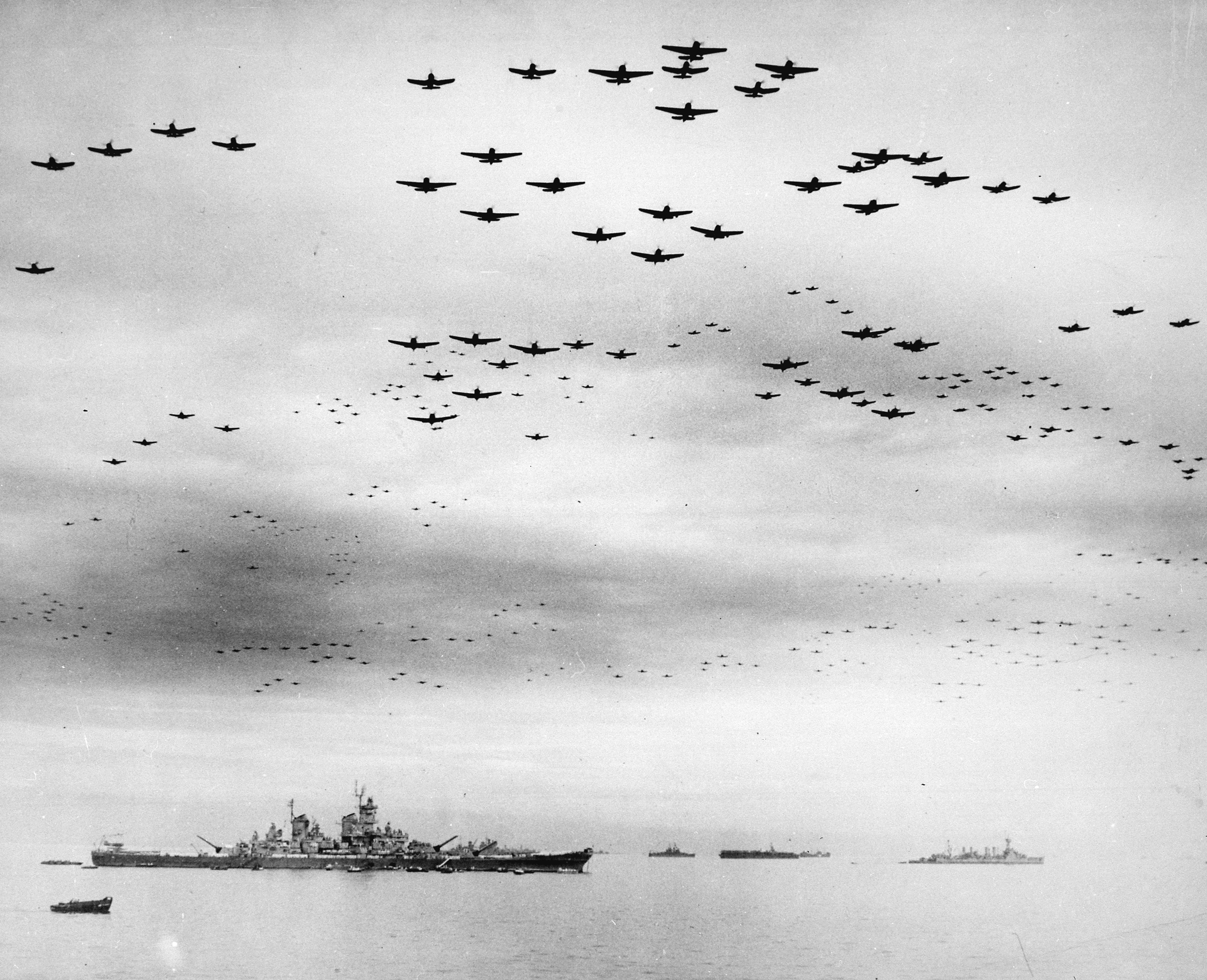 Vought F4U Corsairs and Grumman F6F Hellcats fly in formation past the <em>USS Missouri</em> during surrender ceremonies in Tokyo Bay on Sept. 2, 1945. Photo No. 80-G-421130 courtesy of the National Archives.