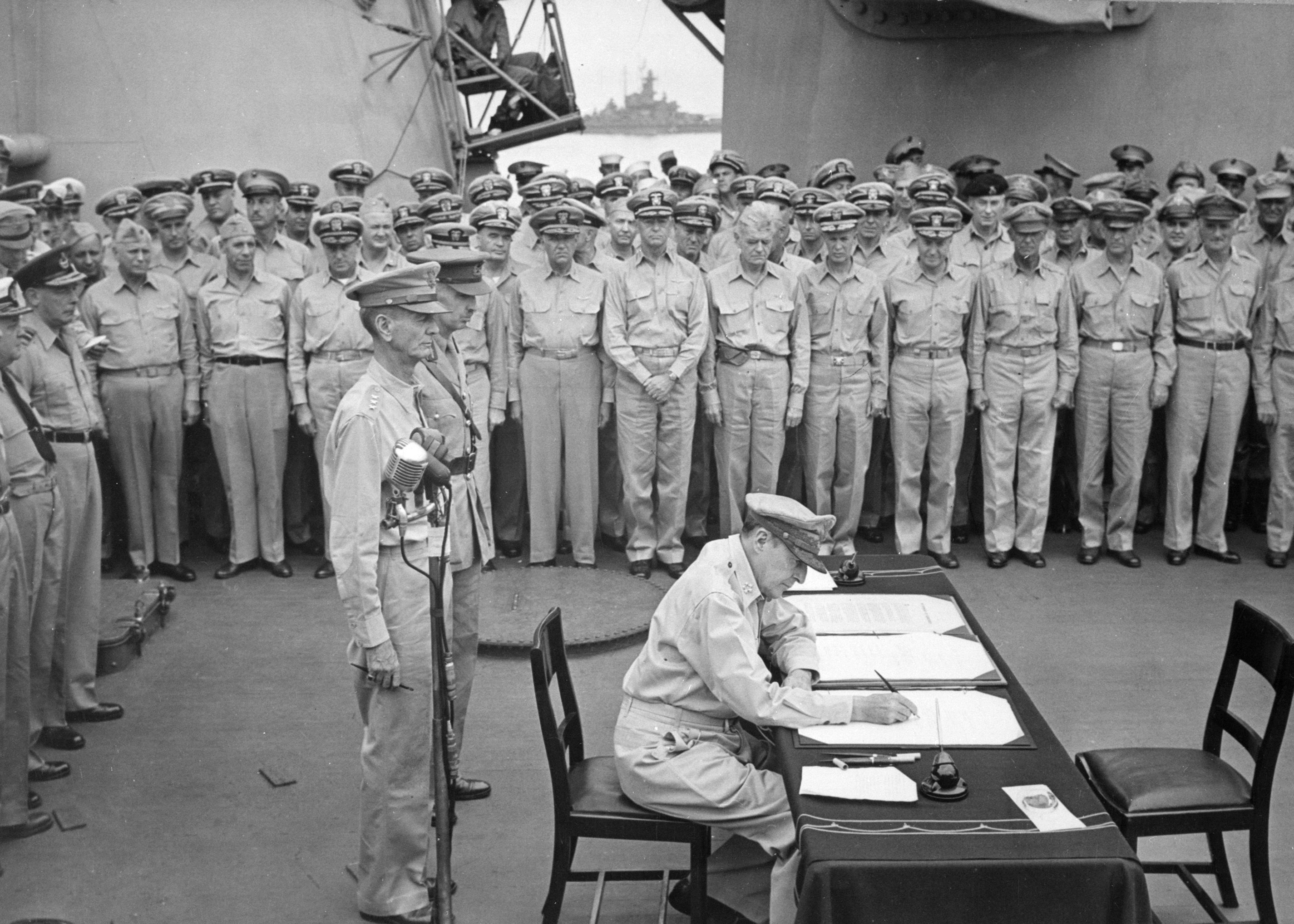 Gen. Douglas MacArthur signs formal surrender documents aboard the <em>USS Missouri</em> during ceremonies in Tokyo Bay on Sept. 2, 1945. Behind MacArthur are Lt. Gen. Jonathan Wainwright and Lt. Gen. A. E. Percival. Photo No. 280-G-348366 courtesy National Archives.