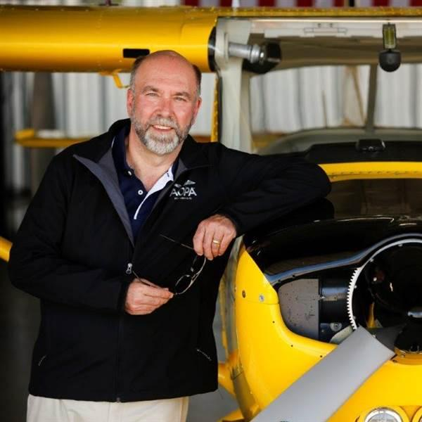 photo of andy miller next to a yellow cessna