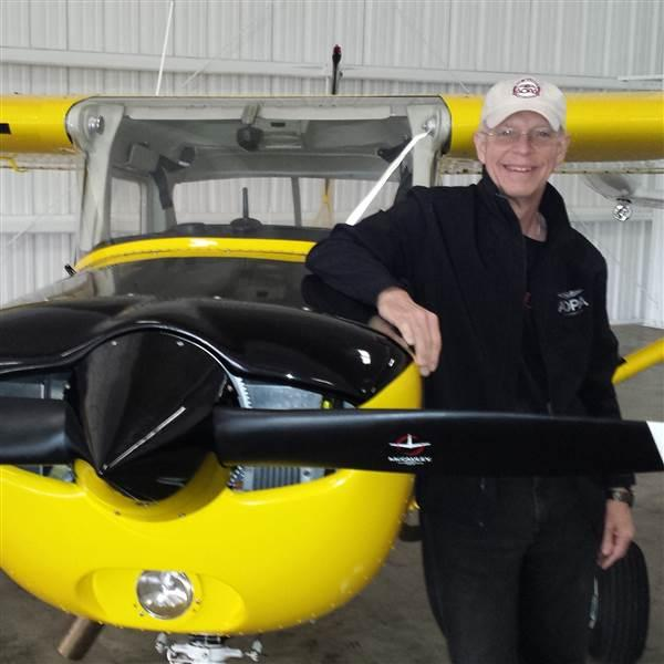 photo of pat brown next to a yellow cessna