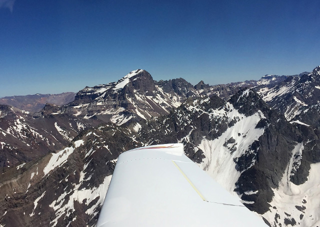 The craggy peaks of the Andes Mountains are framed by the wing of Tomas Vykruta's Cirrus SR22 near Santiago, Chile. Photo courtesy of FlyforMS.org.