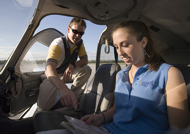 A flight instructor and his student prepare for a training flight in the cockpit of a Piper aircraft. The FAA is on track to meet a June 2016 goal of transitioning to an updated system for those seeking an airplane private pilot certificate. Photo by Mike Fizer.