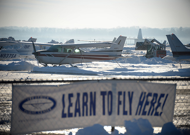 Snow removal equipment is deployed around parked Cessna aircraft during cleanup operations after a mid-Atlantic blizzard brought more than two feet of snow, high winds, and whiteout conditions to AOPA headquarters at Frederick Municipal Airport in Frederick, Maryland. Photo by David Tulis.