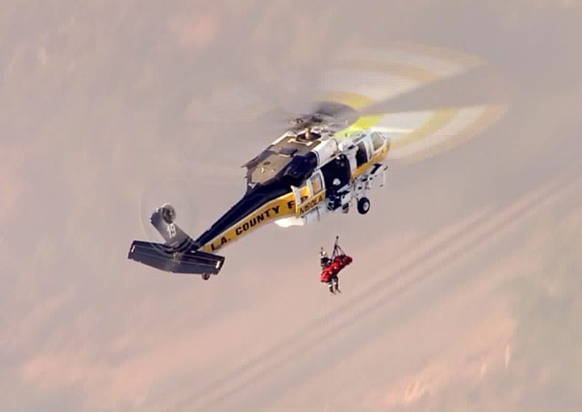 In a dramatic rescue, the County of Los Angeles Fire Department Aviation Unit hoists the driver from the crash site in a Sikorsky S-70A Firehawk. Photo credit: KTLA News via PRNewsFoto/Sikorsky Aircraft