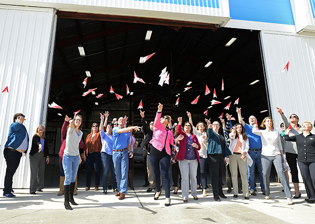 Thirty-four aviation enthusiasts who fashioned 397 pink paper airplanes in 15 minutes in an attempt to set a world record, launch their airplanes from AOPA's National Aviation Community Center in Frederick, Maryland, March 8. Photo by David Tulis.