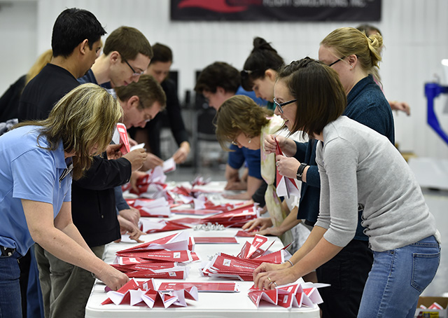 Thirty-four aviation enthusiasts including Karen Hemenway, right, helped fashion 397 pink paper airplanes in 15 minutes in an attempt to set a world record at AOPA's National Aviation Community Center in Frederick, Maryland. Photo by David Tulis.