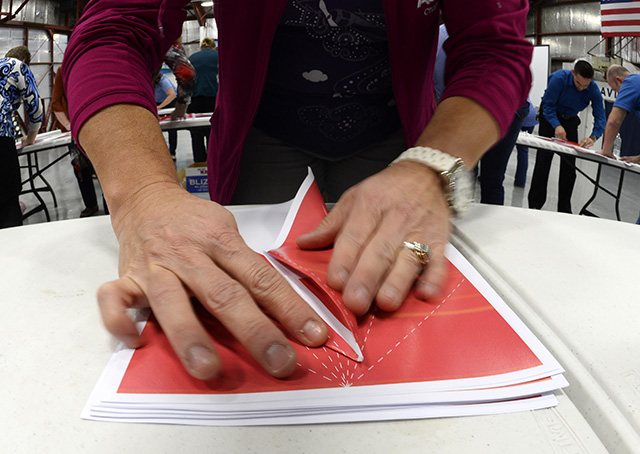 A participant carefully folds a paper airplane along dotted lines to speed construciton during the world record attempt March 8. Photo by David Tulis.
