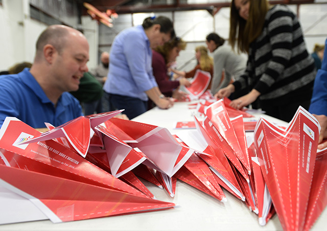Flight instructor Chris Moser joins other pilots and aviation enthusiasts in a world record attempt at paper airplane construction. Photo by David Tulis.