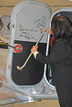 Mira Nair, director of Amelia, autographs the cabin door of Joe Shepherd's Electra Junior.