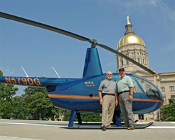 Perdue (right) with CFI Ron Carroll and a Robinson R44 in front of the Georgia capitol. Perdue earned his helicopter rating in 2008.