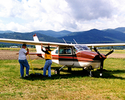 From his home airport in Roundup, Mont., State Sen. Kelly Gebhardt flies out over the Rocky Mountains and the plains. Shown here with his Cessna 210 and twins Derin and Donna at Plains, Mont., in 1998.