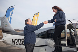 AOPA President Craig Fuller congratulates Karoline Amodeo, winner of the 2008 Get Your Glass Sweepstakes Piper Archer.