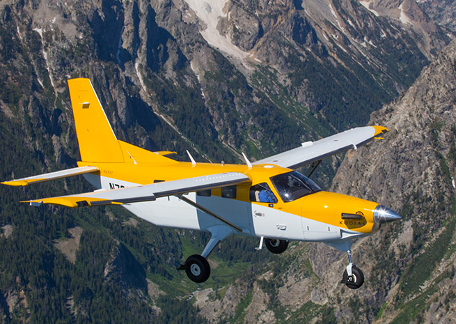 A Kodiak flies over the Tetons in July. Photo by Jim Moore