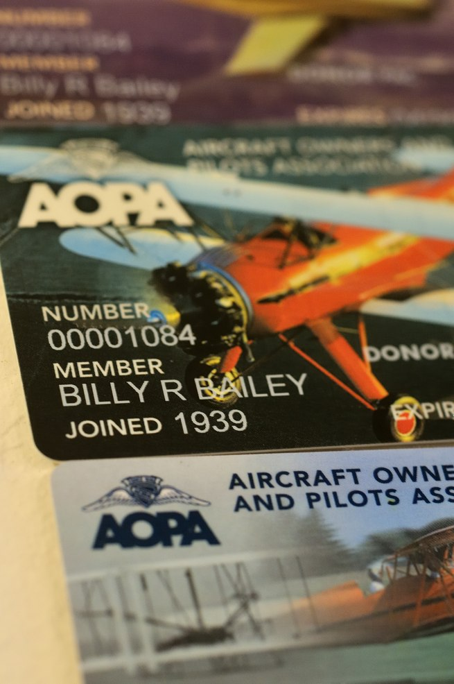 Bill Bailey displays some of his many AOPA membership cards on the wall of his condo.