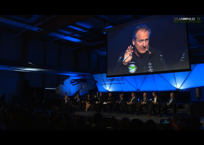 Solar Impulse CEO and pilot André Borschberg (on screen) addresses the crowd gathered for the unveiling of Solar Impulse 2, flanked on stage by project sponsors with the aircraft in the background.
