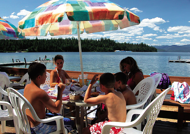 Guests dine on the outdoor deck at Cavanaugh Bay, with views of Priest Lake. Photo by George A. Kounis.