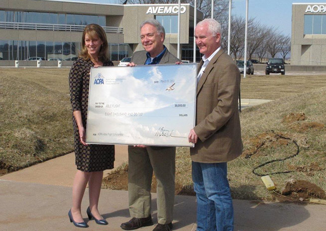 AOPA President Mark Baker (right) and AOPA Foundation Vice President of Strategic Philanthropy Stephanie Kenyon (left) present Able Flight Executive Director Charles Stites with an $8,000 check.
