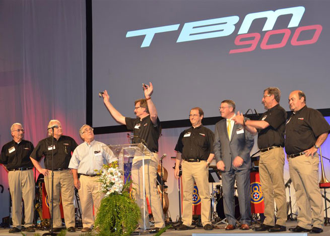 Nicolas Chabbert, senior vice president of the Daher-Socata Business Unit, holds up the keys to the first two TBM 900s in a ceremony at Fantasy of Flight. From left are Ken Dono and Art Maurice of Columbia Aircraft Sales; Larry Glazer, chairman of TBMOPA; Chabbert; Stephane Mayer, CEO of Daher-Socata; Ross Matthews, another new TBM 900 owner; Patrick Daher, chairman and CEO of the Daher Group; and Michel Adam de Villiers, Daher-Socata's vice president of Aircraft Sales.