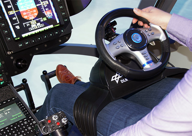 A steering wheel replaces the cyclic control, with an eight-way switch that allows reverse and lateral flight. The pedals control acceleration and deceleration. DLR photo.