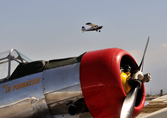 A departure climbs out above a polished T-6 in the static display area.